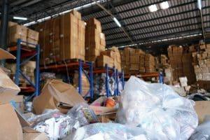 déchets de commerces stockés dans un hangar avec des emballages plastique à l'avant plan